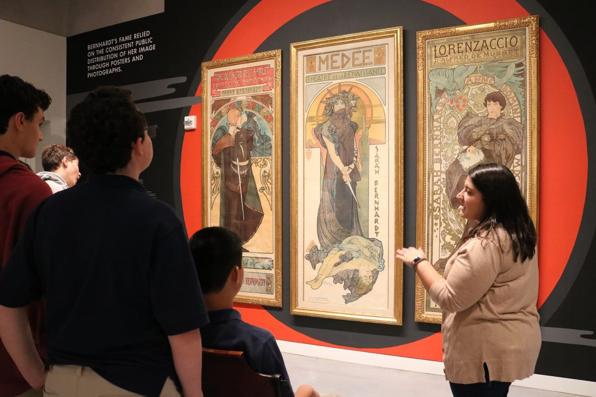 photograph of a group of students and an educator standing in front of three posters
