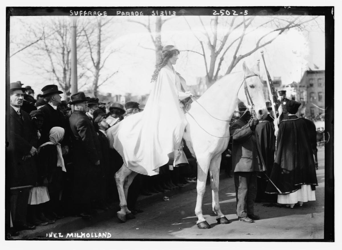 black and white photograph of a woman dressed in white riding a white horse next to a crowd dressed in black