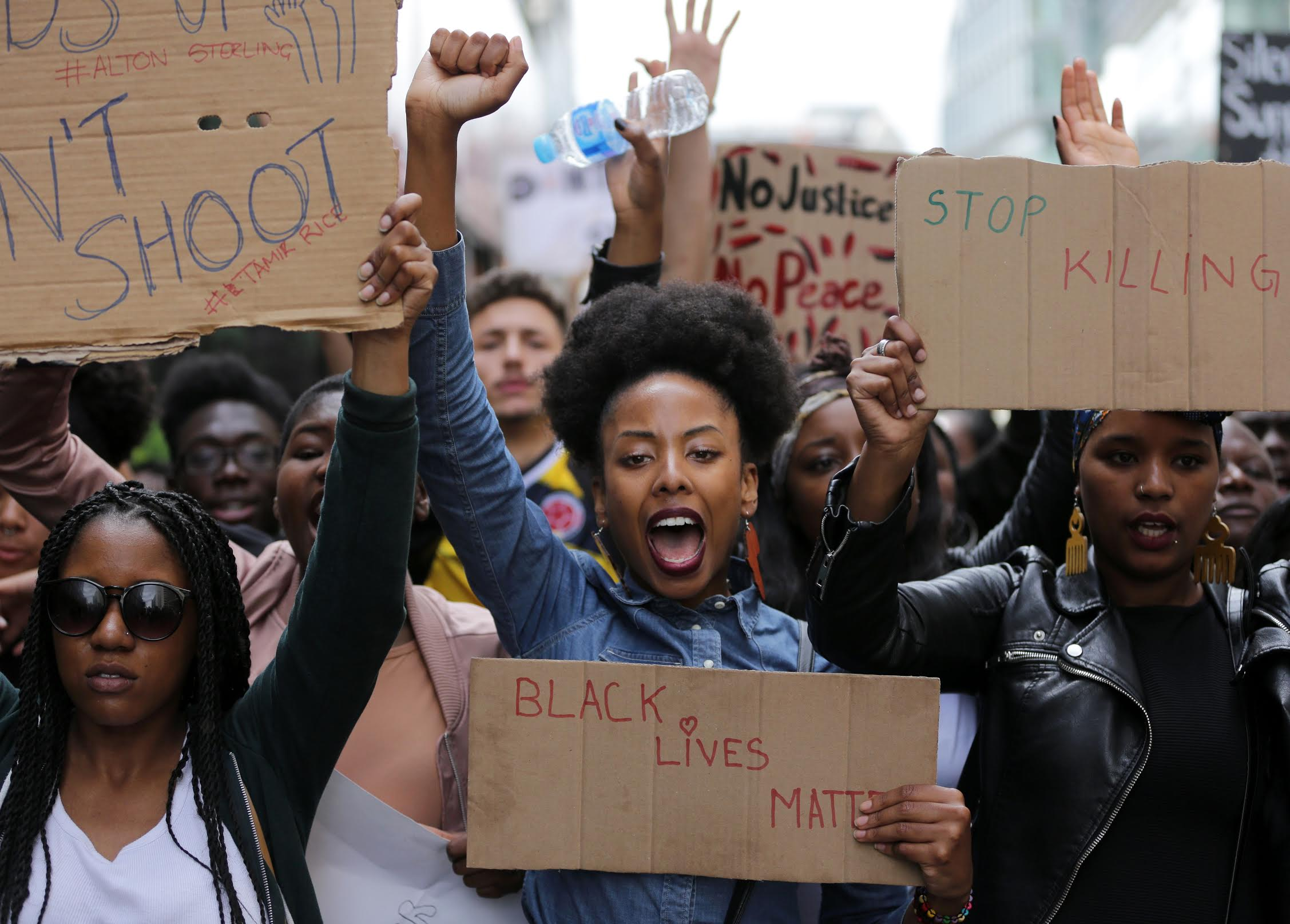 photograph of a protesters holding signs and raising their fists during a Black Lives Matter protest