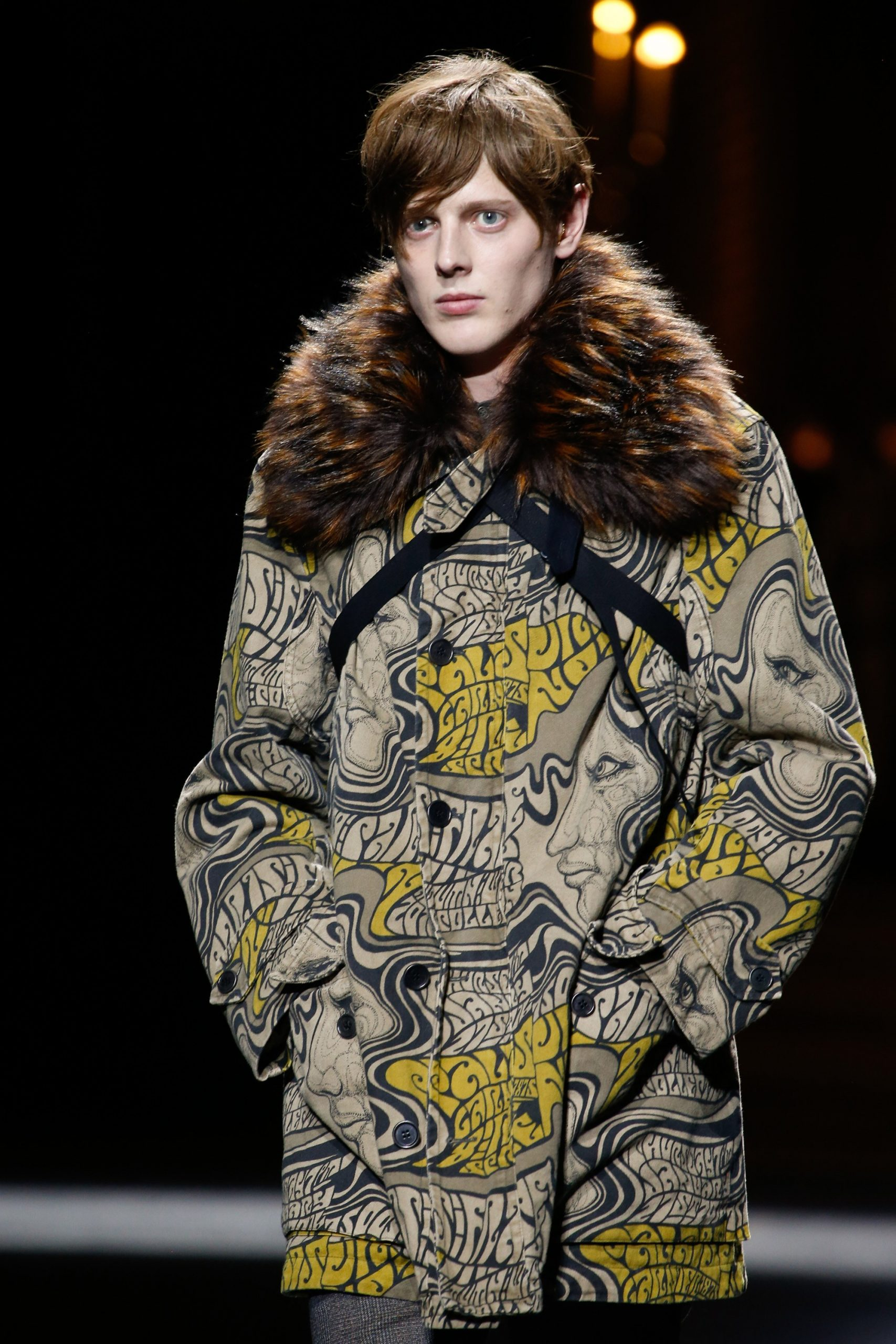 photograph of a male model walking a runway wearing a psychedelic era inspired coat