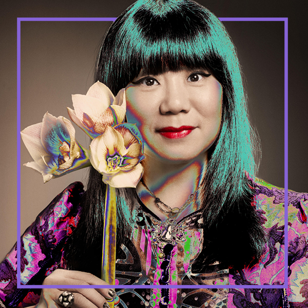 Photo of Anna Sui holding flowers with a developing negative effect throughout