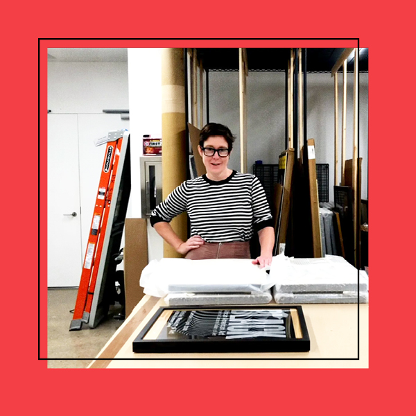 A photo of the archives room in Poster House with the Collections Manager in the center looking at the camera. The photo is framed with a red frame.