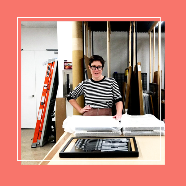 A photo of the archives room in Poster House with the Collections Manager in the center looking at the camera. The photo is framed with a peach frame.