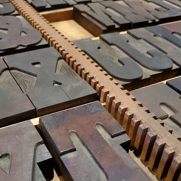 a close-up photograph of wood-type lettering in a storage drawer