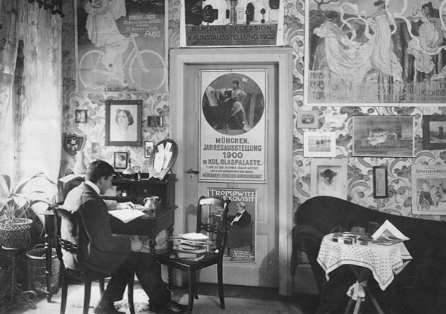 Photograph of a man sitting at a desk with his back to the viewer surrounded by posters