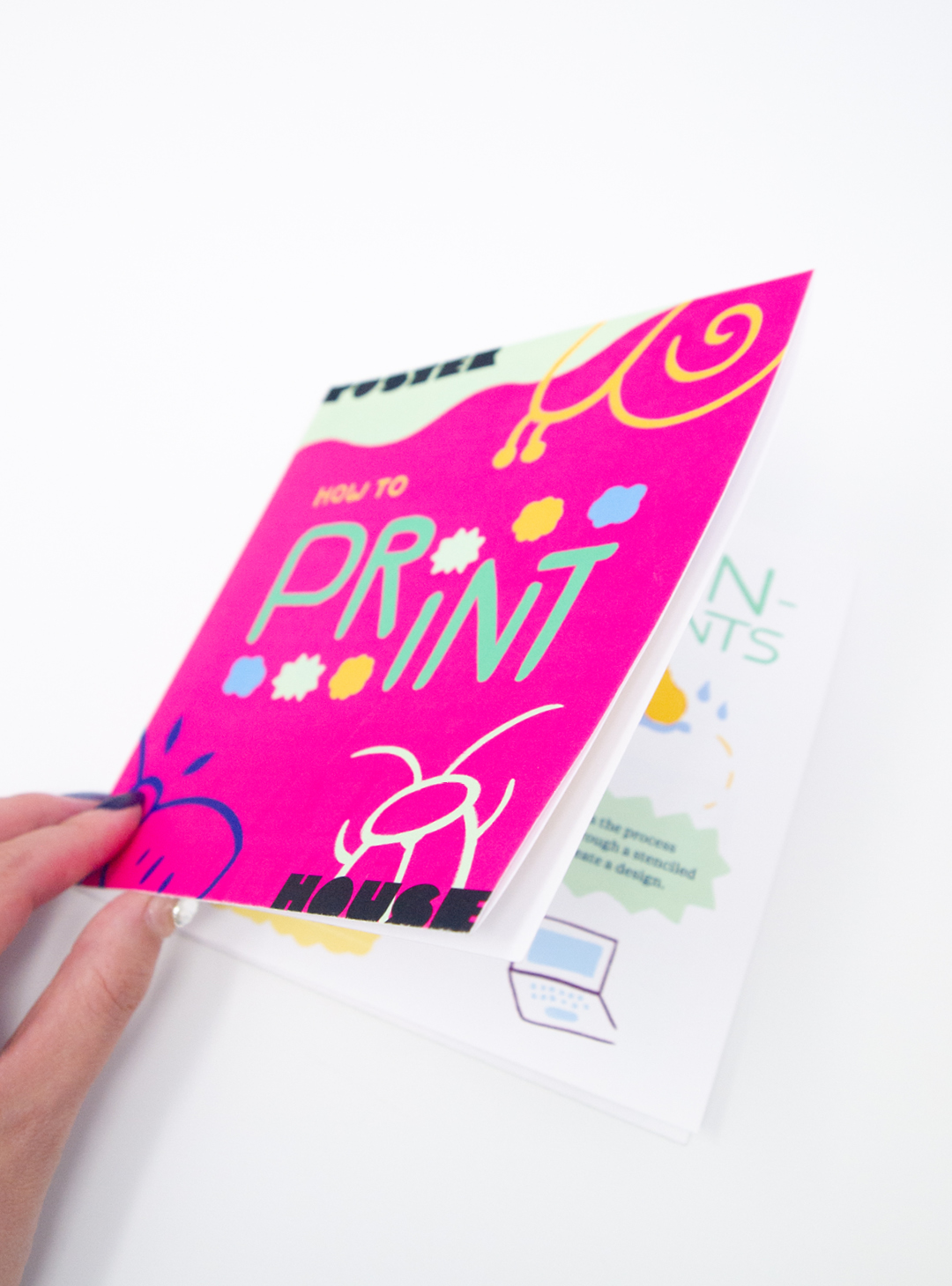 A photograph of the booklet being opened. The cover of the booklet, featuring words